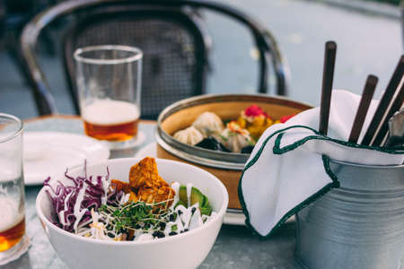 Pan-Asian food - vegetable salad bowl and different dim sums. Lunch for two with beer Stockfoto