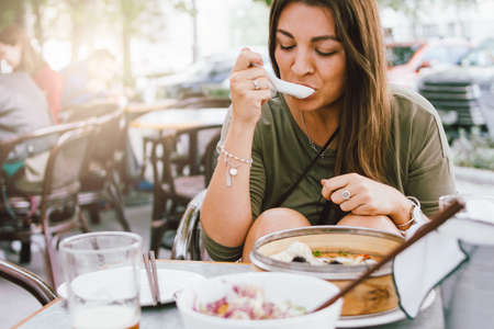 Young smiling brunette girl eating dim sum in a street cafe Stock Photo - 129802191
