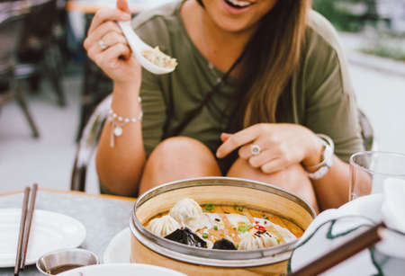 Young smiling brunette girl eating dim sum in a street cafe