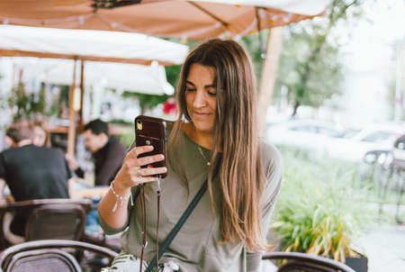Young smiling long hair brunette girl dressed casual using mobile in the street cafe