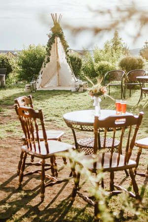 Wooden fabric wigwam decorated with green eucalyptus branches in backyard, event or wedding in boho style