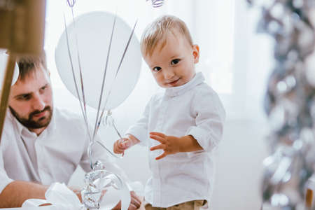 Cute baby boy celebrates his birthday one year at home in a bright interior with his father