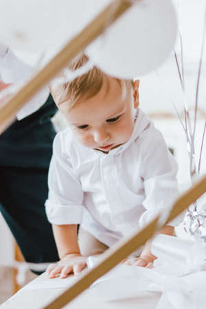 Cute baby boy in white shirt with hands of fother in bright interior, close up portrait Stock fotó