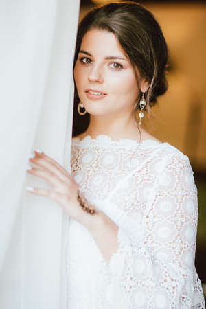 Beautiful smiling bride brunette young woman in the white lace dress near window, close up portrai Archivio Fotografico - 132123335