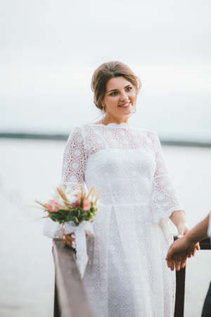 Happy newly married couple, smiling bride brunette young woman with boho style bouquet looking on groom, outdoors