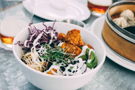 Pan-Asian food - the vegetable salad bowl and different dim sums. Lunch for two with beer Stock fotó