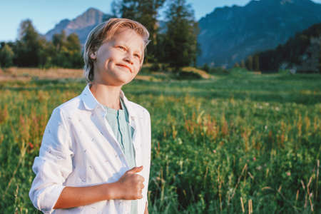 Blonde smiling boy looking at camera on background of wonderful view of the green meadow and mountains, family travel adventure lifestyle Stock fotó