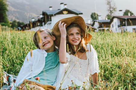 Children brother and sister friends sitting in grass against the background of beautiful houses in mountain, family travel, rural scene