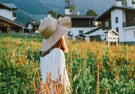 Beautiful romantic preteen girl in straw hat against the background of beautiful houses in the mountain, rural scene at sunset. View from behind, golden hour Stock fotó