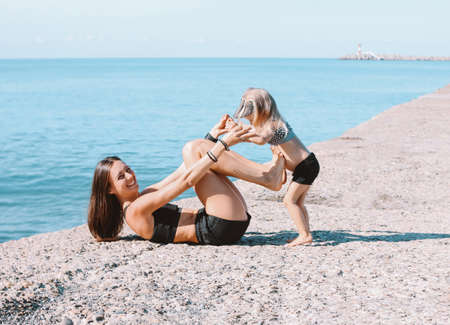 Young fit woman mom with little cute girl exercising on the beach together, healthy lifestyle, sport family