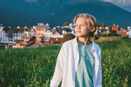 Blonde smiling boy looking at camera on background of wonderful view of the mountain resort, family travel adventure lifestyle