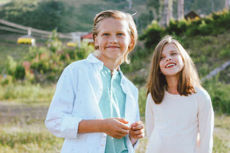 Children brother and sister friends look up with admiration against background of mountain resort, family travel