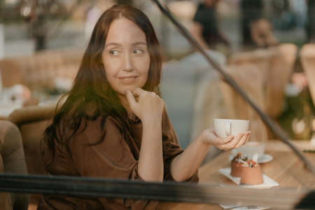 Charming brunette woman with long curly hair sitting at window in cafe with cup of coffee in hands