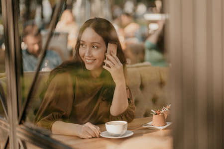 Charming brunette woman with long curly hair sitting at window in cafe with mobile phone in hands 写真素材