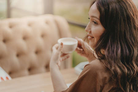 Charming brunette woman with long curly hair sitting at window in cafe with cup of coffee in the hands 写真素材