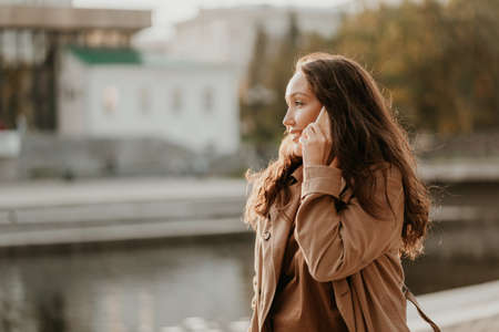 Charming smiling brunette woman with long curly hair dressed casual coat with mobile phone in hands at the city street