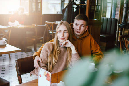Young couple dressed warm casual clothing sitting at the cafe together Фото со стока