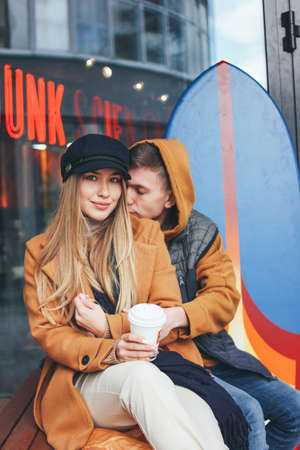 Happy young couple in love teenagers friends dressed in casual style walking together on the city street in cold season