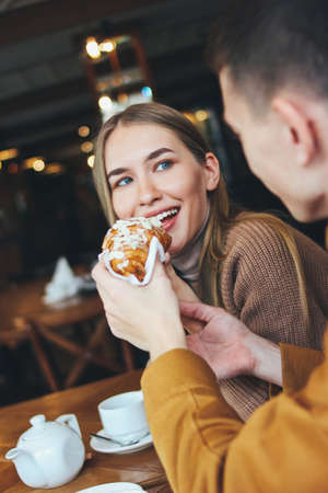 Happy young couple dressed warm casual clothing sitting at cafe together. The man feeds girl a croissant
