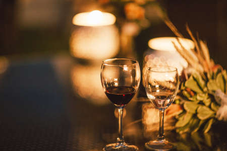 Two glasses of wine on table on the background of wedding bouquet, evening, the end of event