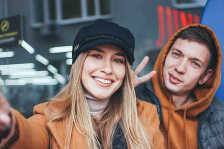 Happy young couple in love teenagers friends dressed in casual style making selfie on the city street in cold season Stock Photo