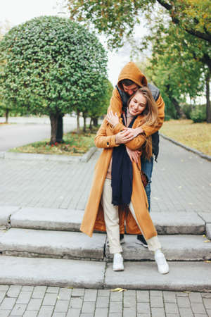 Happy young couple in love teenagers friends dressed in casual style sitting together on the autumn city street