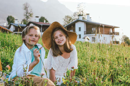 Children brother and sister friends sitting in grass against background of beautiful houses in mountain, family travel, rural scene