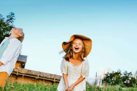 Laughing children brother and sister friends in grass on the background of blue sky, rural scene Stock Photo