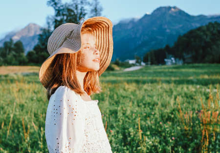 Beautiful romantic preteen girl in straw hat against the background of beautiful houses in mountain, rural scene at sunset