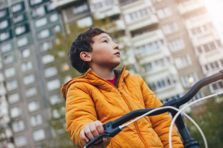 Cute tween boy in yellow jacket on bike in the city street, autumn season Stock Photo