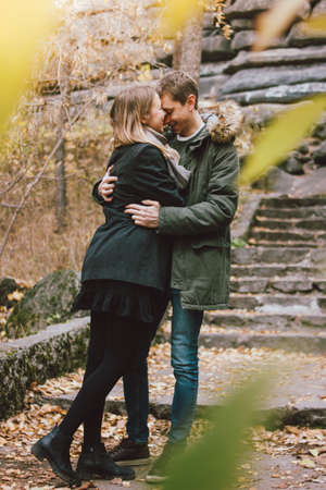 Happy young couple in love friends dressed in casual style walking together on nature park forest in cold season, family advenure travel