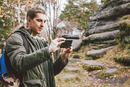 Young male traveler in khaki parka jacket with backpack looks at route in his mobile phone outdoor, travel adventure lifestyle