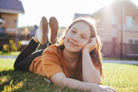 Portrait of smiling teen girl lying on sunny green grass of cottage village on the background Stock Photo