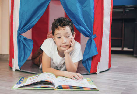 Tween thinking boy with curly hair in toy tent house lying and reading a book at home