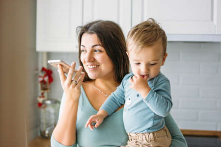 A young carefree woman mom with baby boy in hands dictates voice message on mobile phone in bright kitchen