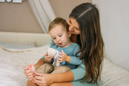 Charming happy little baby boy having fun with mom brunette woman on bed in the bright bedroom Stock Photo