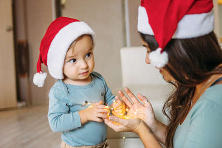 Charming little baby boy with mom brunette woman in santa hat holding garland lights in hands in the home. Christmas family time