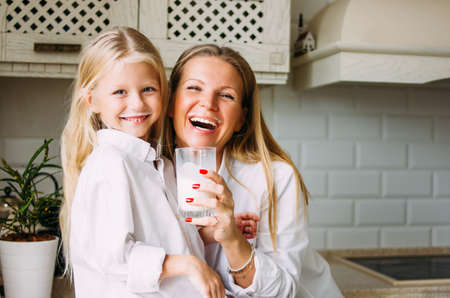Happy blonde long hair mom and daughter drinking milk in kitchen, healthy lifestyle