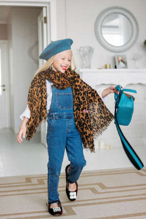 Cute fashion trendy fair hair little girl dressed in the denim overalls, leopard scarf and blue beret with moms accessories. Daughter imitates mom Stock Photo