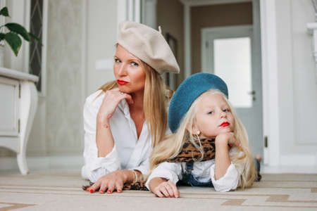 Young funny happy fair long hair mom and her cute girl dressed fashion family look having fun together lying on the floor at living room, happy lifestyle Stock Photo