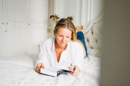 Friendly charming blonde woman with long fair hair in casual clothing reading book on the bed in bright rich interior