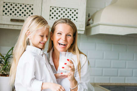Happy blonde long hair mom and daughter drinking milk in the kitchen, healthy lifestyle Stock Photo