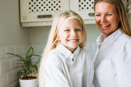 Happy blonde long hair mom and daughter having fun in the kitchen, healthy family lifestyle