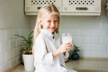 Happy blonde long hair little girl drinking milk in the kitchen, healthy lifestyle Stock Photo