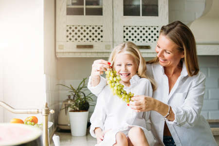 Happy blonde long hair mom and daughter having fun with grapes in the kitchen, healthy family lifestyle