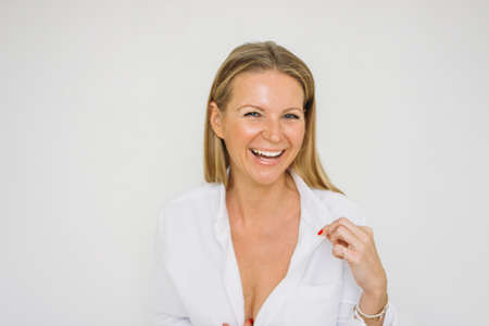 Portrait of happy blonde forty year woman with long hair in the white shirt on wall background isolated