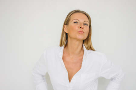 Portrait of happy blonde forty year woman with long hair in white shirt on white wall background isolated Stock Photo