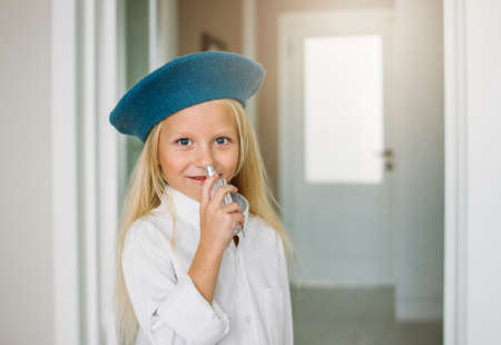 Cute fashion trendy fair hair little girl dressed in the white shirt and blue beret with moms paarfume at home. Daughter imitates mom