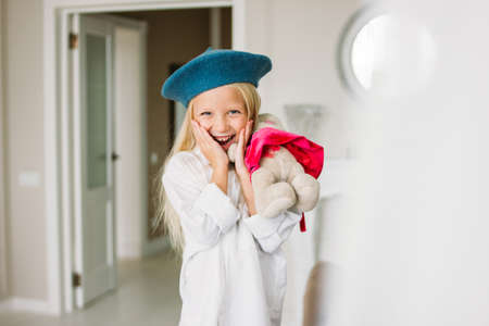 Cute fashion trendy fair hair little girl dressed in white shirt and blue beret with toy in the hands. Daughter imitates mom