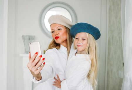 Funny happy fair long hair mom and her cute daughter making selfie together on mobile phone at lliving room, happy family lifestyle Stock Photo